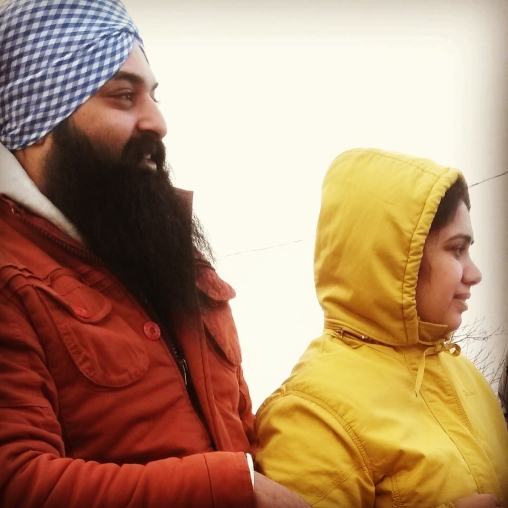 """Mohinder Singh and Bimalpreet Kaur moved to Mississauga from Australia in early 2015. """"We heard it's a great Christmas parade,"""" said Singh. Their daughter, Jasmeh, 2, was having a ball. Photo: Kelly Roche/QEW South Post"""