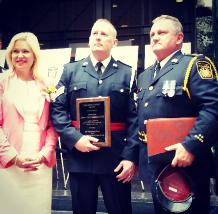 Peel Regional Police Det. Shane McFadden (centre) is awarded the 2016 Police Merit Award. He's flanked by Mississauga Mayor Bonnie Crombie and Deputy Chief Brian Adams at City Hall on Thursday, May 26, 2016. McFadden played a key role in a March 2015 drug seizure, taking 15 kilograms of cocaine off the street. Seven months later, his instinct at a crime scene led to an arrest in a murder case. (Photo: Kelly Roche/QEW South Post)