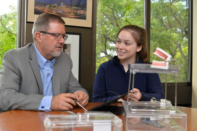 2016 Weston Youth Innovation Award recipient Emma Mogus shows Dr. Maurice Bitran, Ontario Science Centre CEO and chief science officer, her invention: the Tongue-Interface-Communication (TiC). It's a tongue-controlled computer mouse to enable those with physical impairments to communicate freely and effectively online. (Photo: CNW Group/Ontario Science Centre)