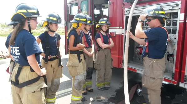 Mississauga firefighter Tom Haines (right,) explains how to operate a pump to a group of teen girls at Camp Ignite on Wednesday, Aug. 10, 2016. (Photo: Kelly Roche/QEW South Post)