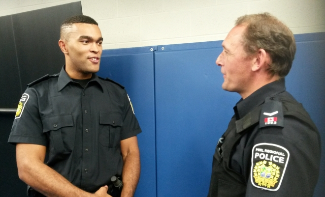 """Kyle Woolery, 24, a Peel Police Recruit Constable chats with Const. Mark Fischer during a training session at the Emil V. Kolb Centre on Tuesday, Aug. 30, 2016. """"I least look forward to getting tased,"""" Woolery said, adding he's most excited to begin his career. (Photo: Kelly Roche/QEW South Post)"""